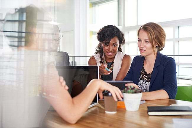 Businesswomen using app at conference room table