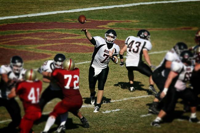 Quarterback throwing football on football field